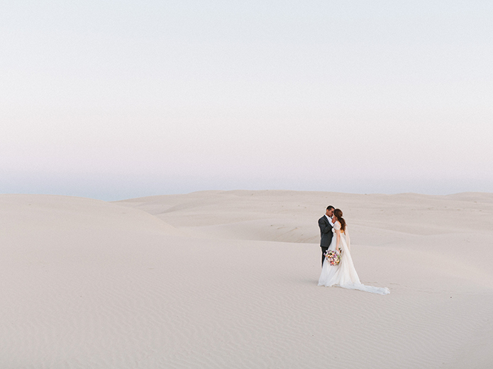 sand-dunes-wedding-shoot-bride-and-groom-kissing-far-away