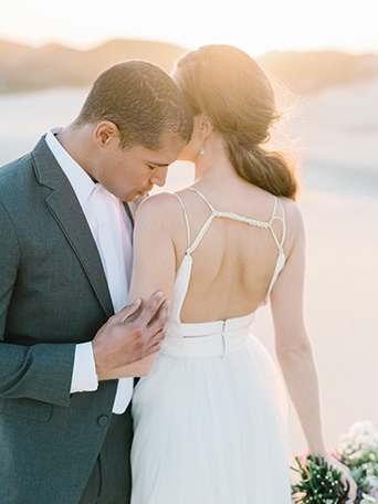 sand-dunes-wedding-shoot-bride-and-groom-kissing-her-shoulder