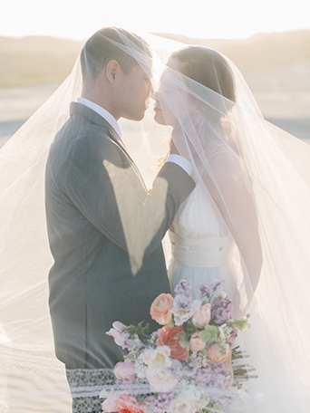 sand-dunes-wedding-shoot-bride-and-groom-under-veil-with-bouquet