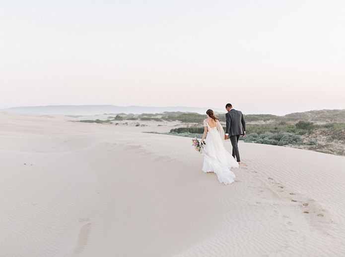 sand-dunes-wedding-shoot-bride-and-groom-walking-holding-hands