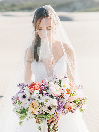 sand-dunes-wedding-shoot-bride-looking-at-bouquet-with-veil-on