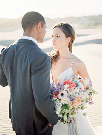 sand-dunes-wedding-shoot-bride-looking-at-groom-holding-bouquet