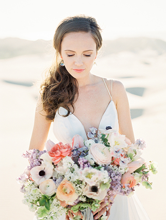 sand-dunes-wedding-shoot-bride-looking-down-at-bouquet