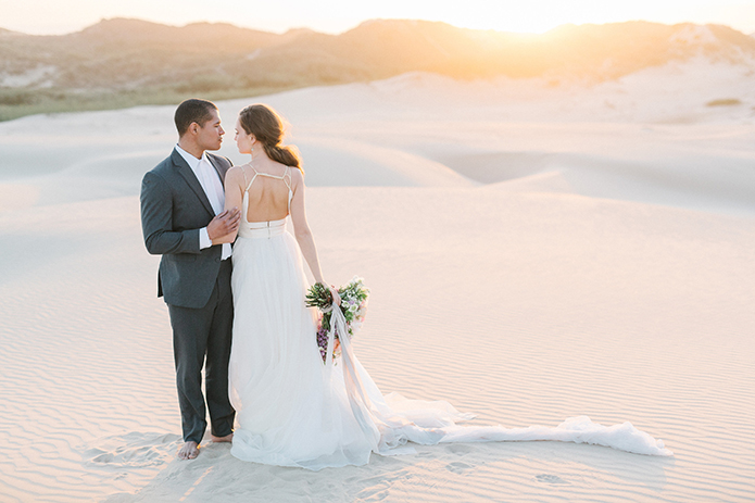 sand-dunes-wedding-shoot-groom-and-back-of-bride