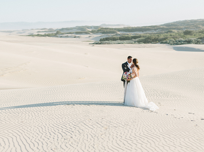 sand-dunes-wedding-shoot-groom-grabbing-bride-far-away-shot