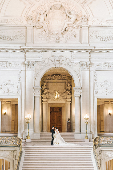 San-francisco-glamorous-wedding-at-city-hall-bride-and-groom-standing-on-stairs-far-away