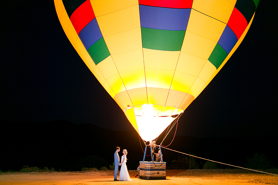 Sweet-oaks-ranch-outdoor-wedding-shoot-bride-and-groom-standing-by-hot-air-balloon-holding-hands