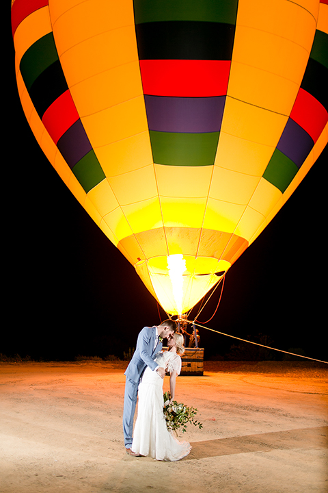 Sweet-oaks-ranch-outdoor-wedding-shoot-bride-and-groom-standing-by-hot-air-balloon-hugging