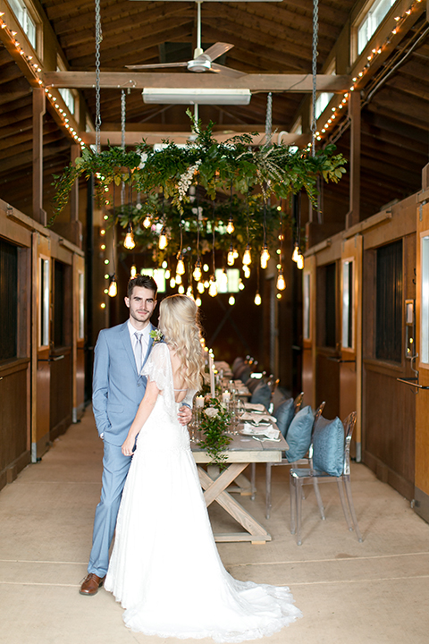 Sweet-oaks-ranch-outdoor-wedding-shoot-bride-and-groom-standing-by-table