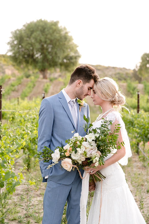 Sweet-oaks-ranch-outdoor-wedding-shoot-bride-and-groom-standing-hugging-holding-bouquet