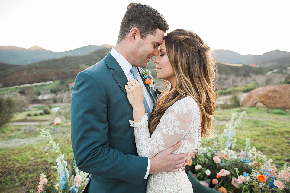 Malibu-wedding-shoot-at-triunfo-creek-vineyards-bride-and-groom-on-blanket-hugging-and-smiling