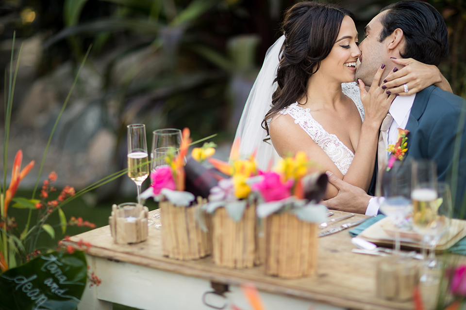 Glamorous-backyard-wedding-shoot-at-a-private-estate-bride-and-groom-kissing-at-table