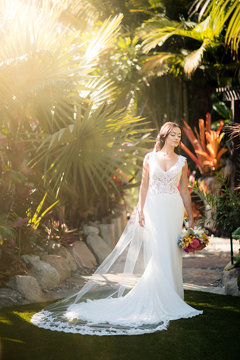 Glamorous-backyard-wedding-shoot-at-a-private-estate-bride-mermaid-style-gown-with-lace-detail-holding-bouquet