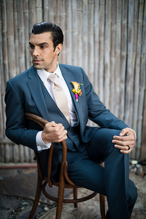 Glamorous-backyard-wedding-shoot-at-a-private-estate-groom-slate-blue-suit-with-long-champagne-tie-sitting-in-chair