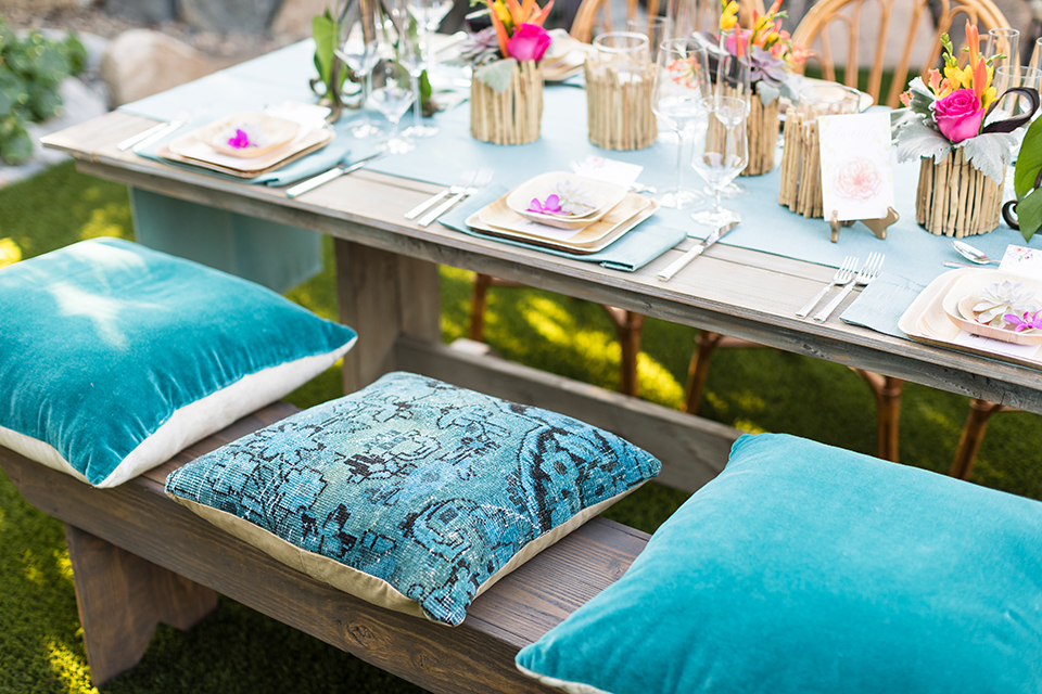 Glamorous-backyard-wedding-shoot-at-a-private-estate-reception-set-up-with-light-brown-wood-table-with-bench-and-pillow-decor
