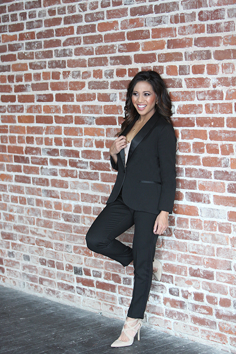 Womens-tuxedo-styled-shoot-at-franciscan-gardens-bride-black-tuxedo-standing-against-wall