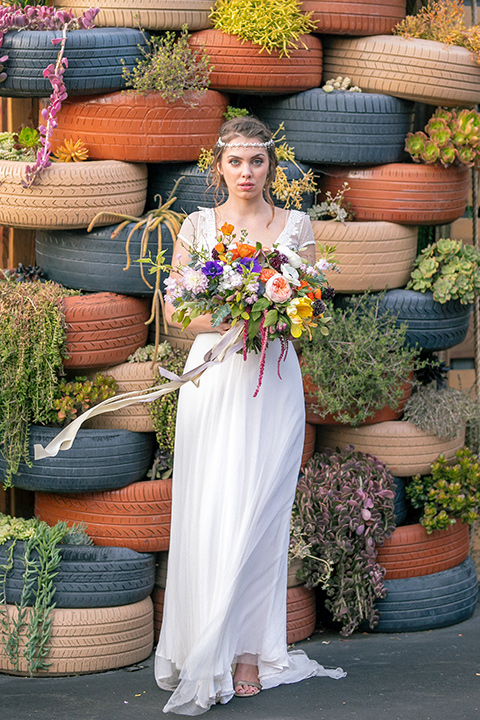 lot-8-colorful-romance-shoot-bride-alone-by-colorful-tires-bride-in-a-bohemian-style-dress-with-capped-sleeves-a-headpeice-and-hair-in-a-bohemian-braid