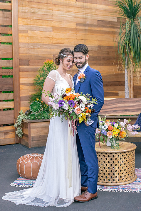 lot-8-colorful-romance-shoot-bride-and-groom-both-eyes-closed-touching-heads-full-body-shot-bride-in-a-bohemian-style-dress-with-capped-sleeves-a-headpeice-and-hair-in-a-bohemian-braid-groom-in-a-cobalt-suit-with-orange-florals-and-a-bolo-tie