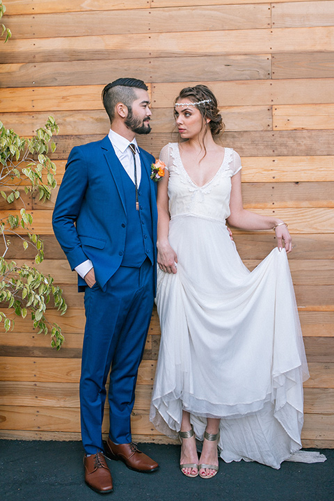 lot-8-colorful-romance-shoot-bride-and-groom-bride-holding-up-her-dress-bride-in-a-bohemian-style-dress-with-capped-sleeves-a-headpeice-and-hair-in-a-bohemian-braid-groom-in-a-cobalt-suit-with-orange-florals-and-a-bolo-tie