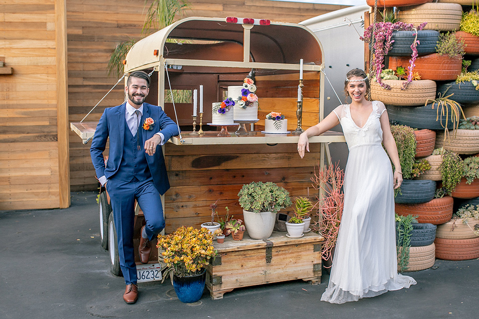 lot-8-colorful-romance-shoot-bride-and-groom-by-bus-bride-in-a-bohemian-style-dress-with-capped-sleeves-a-headpeice-and-hair-in-a-bohemian-braid-groom-in-a-cobalt-suit-with-orange-florals-and-a-bolo-tie