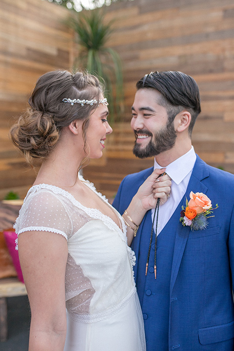 lot-8-colorful-romance-shoot-bride-and-groom-close-up-smiling-at-each-other-bride-in-a-bohemian-style-dress-with-capped-sleeves-a-headpeice-and-hair-in-a-bohemian-braid-groom-in-a-cobalt-suit-with-orange-florals-and-a-bolo-tie