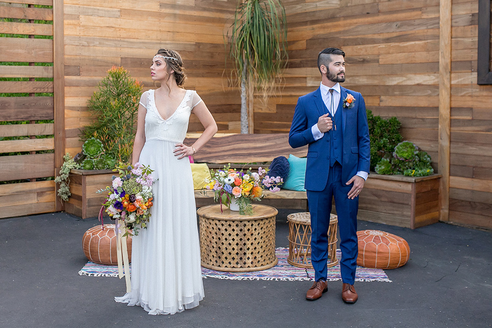 lot-8-colorful-romance-shoot-bride-and-groom-looking-in-different-directions-bride-in-a-bohemian-style-dress-with-capped-sleeves-a-headpeice-and-hair-in-a-bohemian-braid-groom-in-a-cobalt-suit-with-orange-florals-and-a-bolo-tie