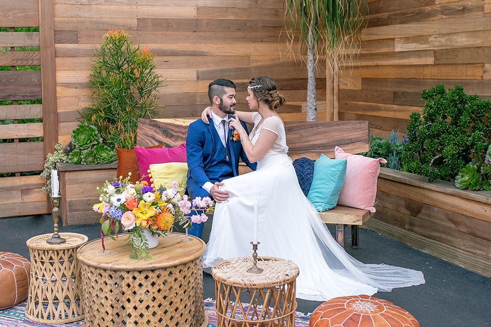 lot-8-colorful-romance-shoot-bride-and-groom-sitting-on-couch-with-colorful-cushions-all-around-them-bride-in-a-bohemian-style-dress-with-capped-sleeves-a-headpeice-and-hair-in-a-bohemian-braid-groom-in-a-cobalt-suit-with-orange-florals-and-a-bolo-tie