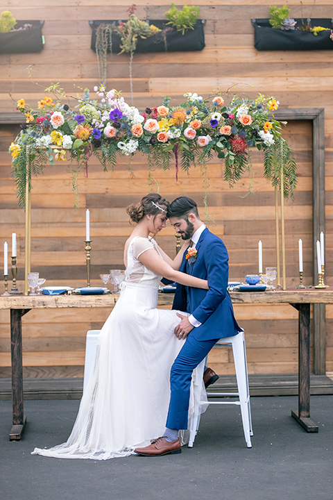 lot-8-colorful-romance-shoot-bride-and-groom-straight-on-shot-with-heads-touching-on-bar-stools-bride-in-a-bohemian-style-dress-with-capped-sleeves-a-headpeice-and-hair-in-a-bohemian-braid-groom-in-a-cobalt-suit-with-orange-florals-and-a-bolo-tie