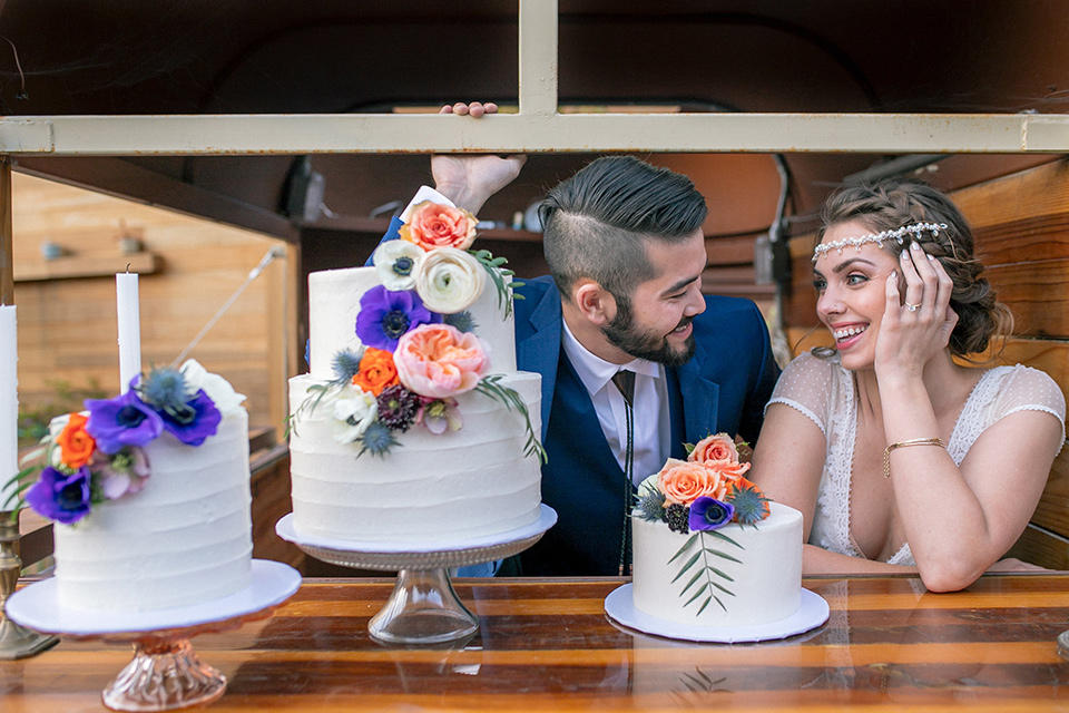 lot-8-colorful-romance-shoot-bride-and-groom-with-cakes-bride-in-a-bohemian-style-dress-with-capped-sleeves-a-headpeice-and-hair-in-a-bohemian-braid-groom-in-a-cobalt-suit-with-orange-florals-and-a-bolo-tie