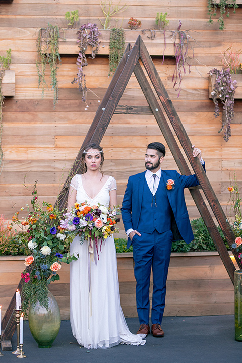 lot-8-colorful-romance-shoot-ceremony-decor-groom-hand-on-arch-bride-in-a-bohemian-style-dress-with-capped-sleeves-a-headpeice-and-hair-in-a-bohemian-braid-groom-in-a-cobalt-suit-with-orange-florals-and-a-bolo-tie
