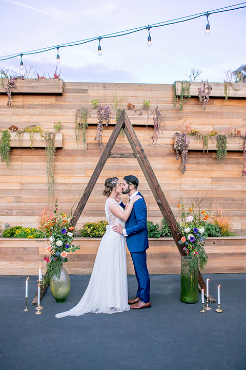 lot-8-colorful-romance-shoot-ceremony-space-bride-in-a-bohemian-style-dress-with-capped-sleeves-a-headpeice-and-hair-in-a-bohemian-braid-groom-in-a-cobalt-suit-with-orange-florals-and-a-bolo-tie
