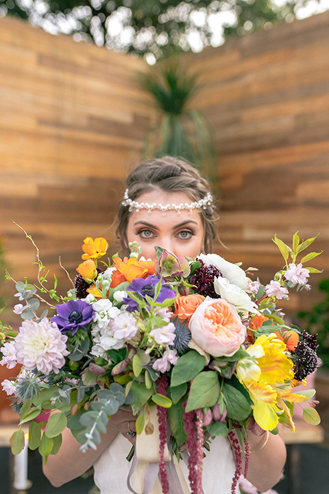 lot-8-colorful-romance-shoot-close-up-of-bride-and-florals-bride-in-a-bohemian-style-dress-with-capped-sleeves-a-headpeice-and-hair-in-a-bohemian-braid