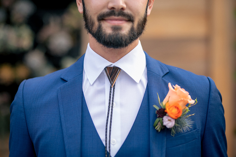 lot-8-colorful-romance-shoot-close-up-on-bolo-tie-groom-in-a-cobalt-suit-with-orange-florals-and-a-bolo-tie