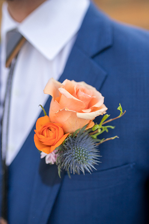 lot-8-colorful-romance-shoot-close-up-on-groom-florals-groom-in-a-cobalt-suit-with-orange-florals-and-a-bolo-tie