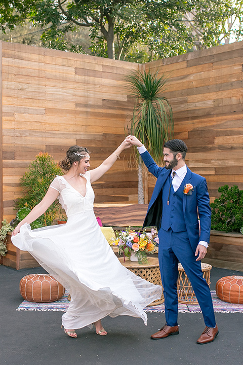lot-8-colorful-romance-shoot-couple-twirling-second-time-around-bride-in-a-bohemian-style-dress-with-capped-sleeves-a-headpeice-and-hair-in-a-bohemian-braid-groom-in-a-cobalt-suit-with-orange-florals-and-a-bolo-tie