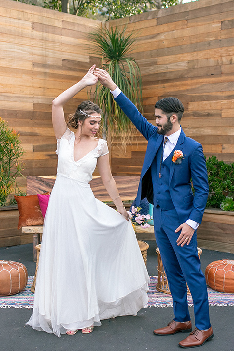 lot-8-colorful-romance-shoot-couple-twirling-bride-in-a-bohemian-style-dress-with-capped-sleeves-a-headpeice-and-hair-in-a-bohemian-braid-groom-in-a-cobalt-suit-with-orange-florals-and-a-bolo-tie