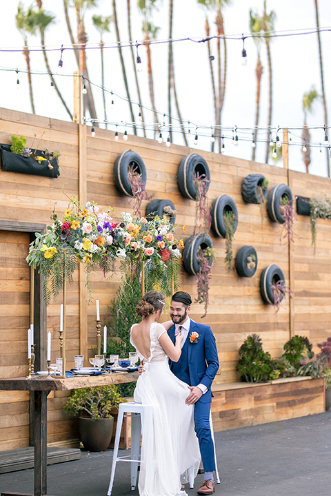 lot-8-colorful-romance-shoot-far-away-shot-bride-and-groom-sitting-on-stools-tires-in-background-bride-in-a-bohemian-style-dress-with-capped-sleeves-a-headpeice-and-hair-in-a-bohemian-braid-groom-in-a-cobalt-suit-with-orange-florals-and-a-bolo-tie