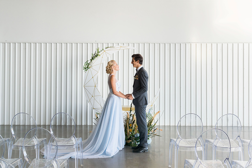 hangar-21-bride-and-groom-at-ceremony-bride-wearing-a-blue-dress-with-lace-details-on-the-bodice-and-flowing-light-blue-material-for-the-skirt-grooom-in-a-charcoal-tuxedo-with-a-matching-charcoal-tie