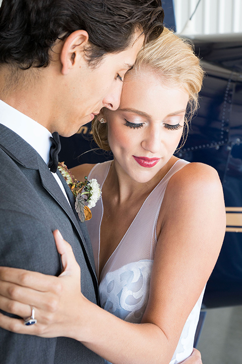 hangar-21-bride-and-groom-close-up-bride-wearing-a-blue-dress-with-lace-details-on-the-bodice-and-flowing-light-blue-material-for-the-skirt-grooom-in-a-charcoal-tuxedo-with-a-matching-charcoal-tie
