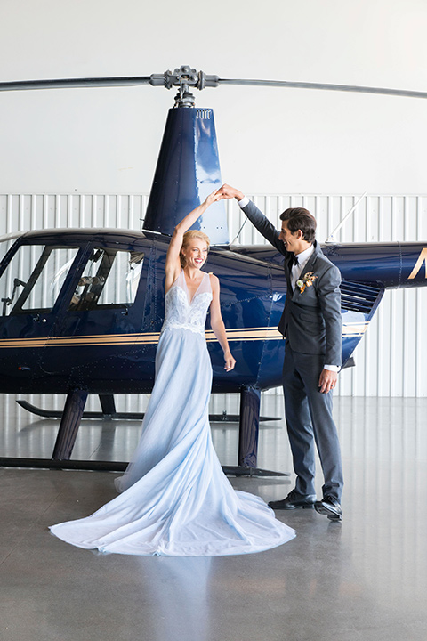 hangar-21-bride-and-groom-dancing-by-helicopter-bride-wearing-a-blue-dress-with-lace-details-on-the-bodice-and-flowing-light-blue-material-for-the-skirt-grooom-in-a-charcoal-tuxedo-with-a-matching-charcoal-tie