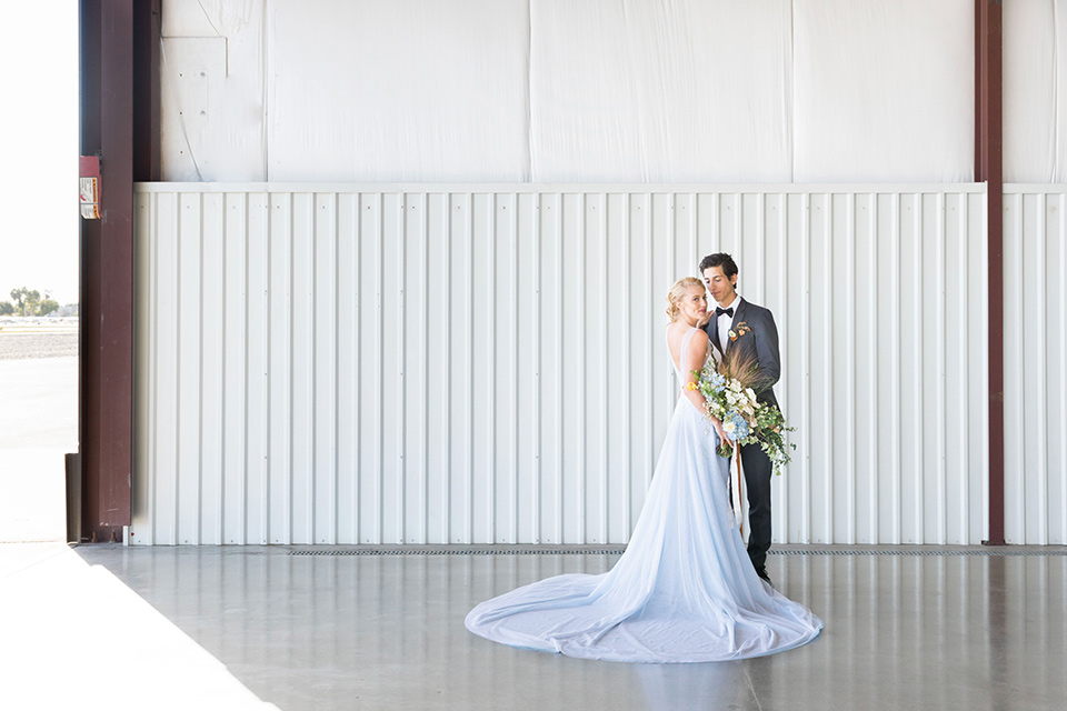 hangar-21-bride-and-groom-in-white-space-bride-wearing-a-blue-dress-with-lace-details-on-the-bodice-and-flowing-light-blue-material-for-the-skirt-grooom-in-a-charcoal-tuxedo-with-a-matching-charcoal-tie