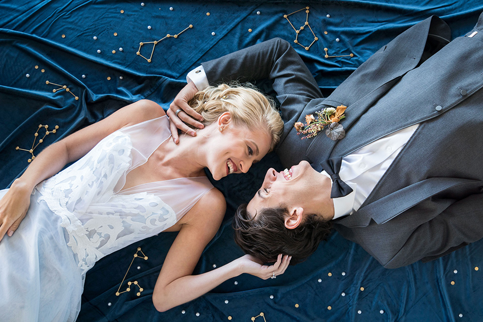 hangar-21-bride-and-groom-laying-on-blue-fabric-bride-wearing-a-blue-dress-with-lace-details-on-the-bodice-and-flowing-light-blue-material-for-the-skirt-grooom-in-a-charcoal-tuxedo-with-a-matching-charcoal-tie