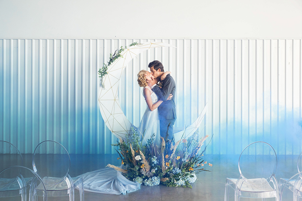 hangar-21-ceremony-brode-and-groom-kissing-with-smoke-bomb-behind-them-a-blue-dress-with-lace-details-on-the-bodice-and-flowing-light-blue-material-for-the-skirt-grooom-in-a-charcoal-tuxedo-with-a-matching-charcoal-tie
