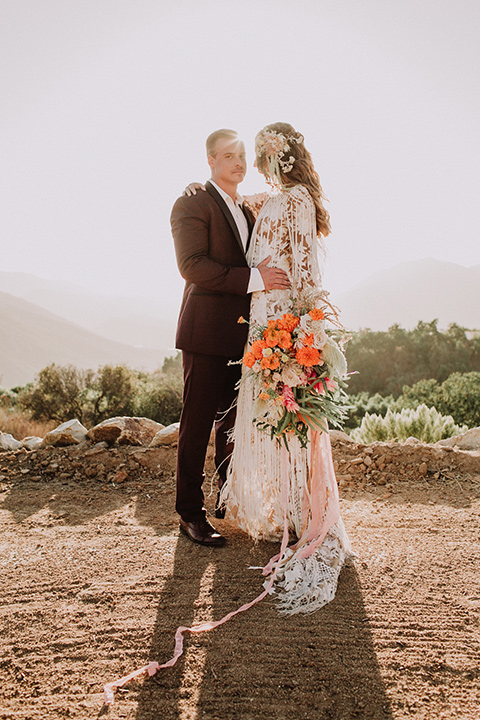 hey-babe-ranch-bride-and-groom-groom-looking-at-camera-bride-looking-at-him-bride-in-a-bohemian-gown-with-lace-and-fringe-detailing-and-hair-in-a-loose-wave-groom-in-a-burgundy-tuxedo-with-black-satin-truim-and-his-tie-undone-for-a-relaxed-look