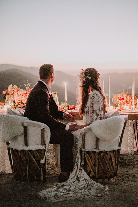 hey-babe-ranch-bride-and-groom-looking-into-the-distance-back-to-camera-bride-looking-at-him-bride-in-a-bohemian-gown-with-lace-and-fringe-detailing-and-hair-in-a-loose-wave-groom-in-a-burgundy-tuxedo-with-black-satin-truim-and-his-tie-undone-for-a-relaxed-look
