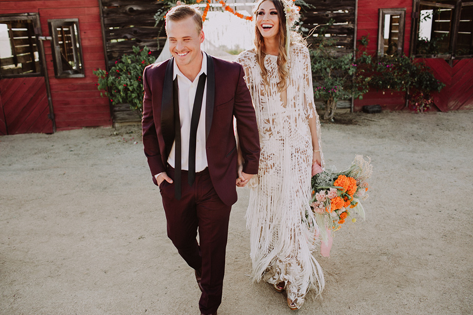 hey-babe-ranch-bride-and-groom-walking-away-and-laughing-bride-in-a-bohemian-gown-with-lace-and-fringe-detailing-and-hair-in-a-loose-wave-groom-in-a-burgundy-tuxedo-with-black-satin-truim-and-his-tie-undone-for-a-relaxed-look