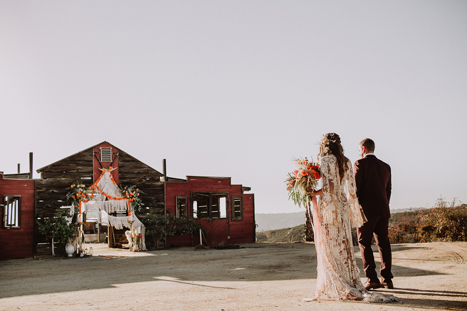 hey-babe-ranch-bride-and-groom-walking-towards-barn-bride-in-a-bohemian-gown-with-lace-and-fringe-detailing-and-hair-in-a-loose-wave-groom-in-a-burgundy-tuxedo-with-black-satin-truim-and-his-tie-undone-for-a-relaxed-look