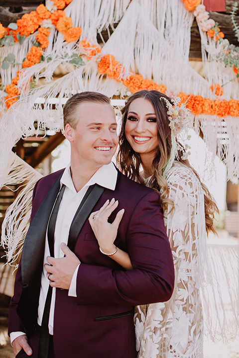 hey-babe-ranch-bride-andgroom-embracing-bride-behind-him-both-smiling-bride-in-a-bohemian-gown-with-lace-and-fringe-detailing-and-hair-in-a-loose-wave-groom-in-a-burgundy-tuxedo-with-black-satin-truim-and-his-tie-undone-for-a-relaxed-look