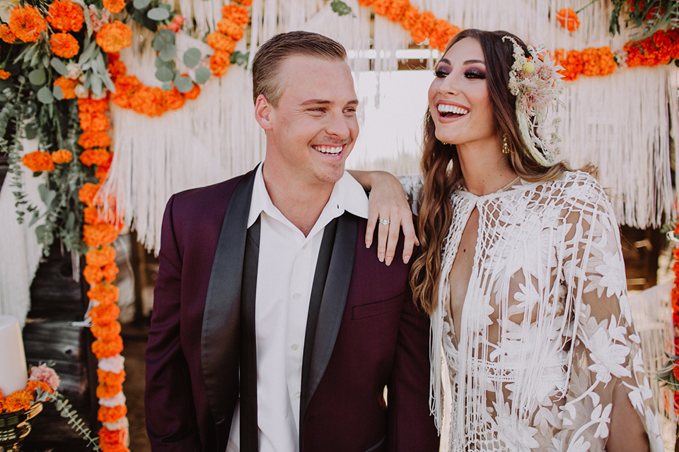 hey-babe-ranch-bride-andgroom-laughing-close-up-bride-in-a-bohemian-gown-with-lace-and-fringe-detailing-and-hair-in-a-loose-wave-groom-in-a-burgundy-tuxedo-with-black-satin-truim-and-his-tie-undone-for-a-relaxed-look