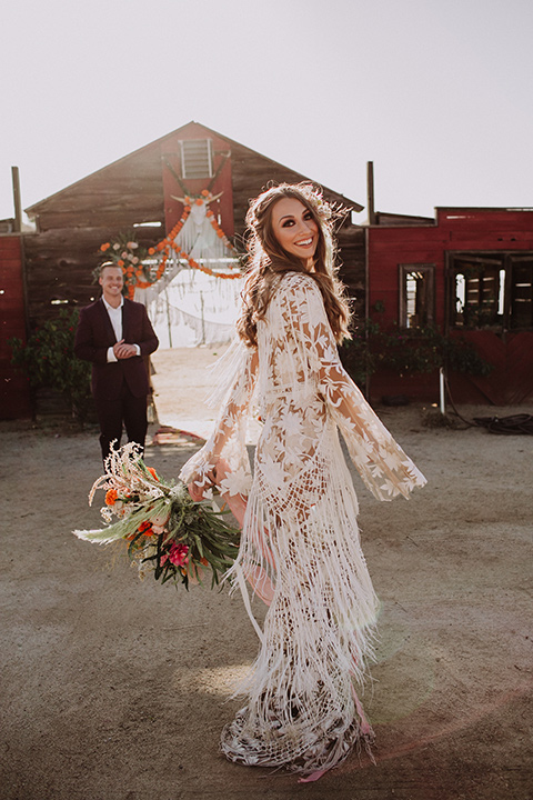 hey-babe-ranch-bride-twirling-groom-behind-her-bride-looking-at-camera-bride-in-a-bohemian-gown-with-lace-and-fringe-detailing-and-hair-in-a-loose-wave-groom-in-a-burgundy-tuxedo-with-black-satin-truim-and-his-tie-undone-for-a-relaxed-look